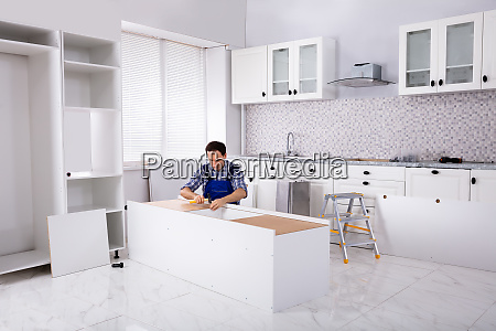 carpenter assembling furniture in new house