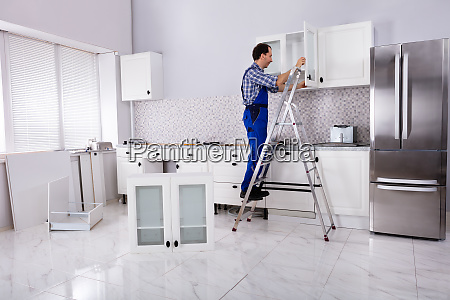 carpenter assembling cabinet on wall in