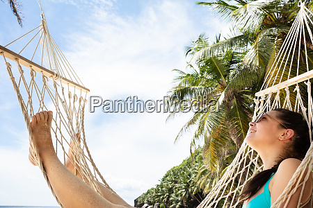 smiling young woman lying on hammock