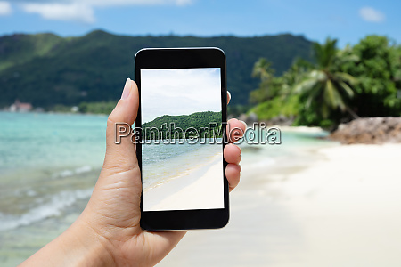 person taking photograph on mobile phone