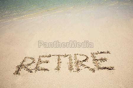 retire text on sand beach
