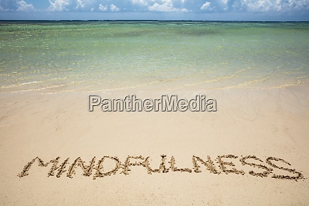 mindfulness written text on sand at