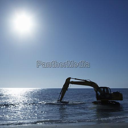 excavator digging in the ocean