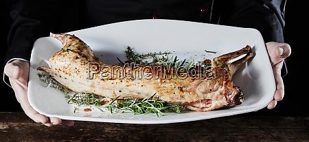 chef holding fresh roasted wild rabbit