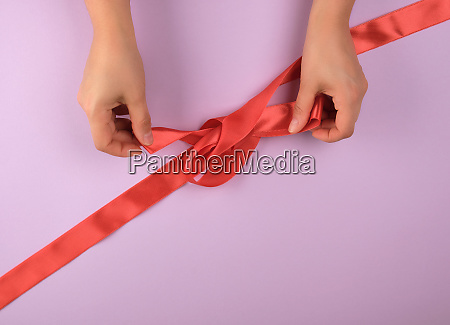 two female hands tie a bow
