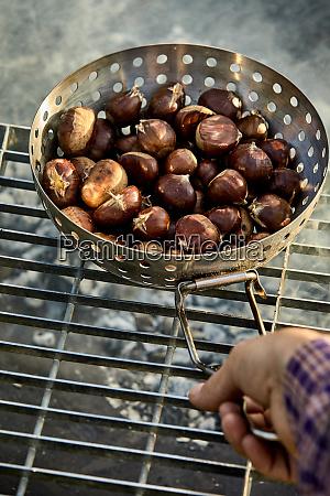 man roasting fresh sweet chestnuts in