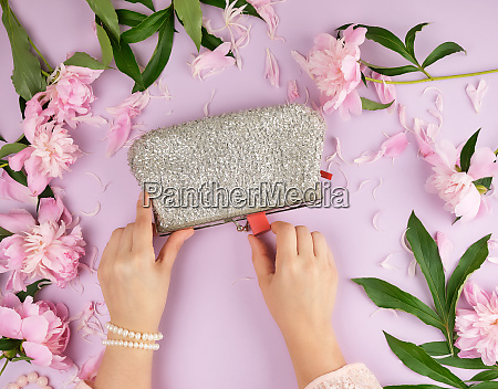 womens hands hold a silver clutch