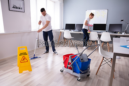 smiling two young janitor cleaning the