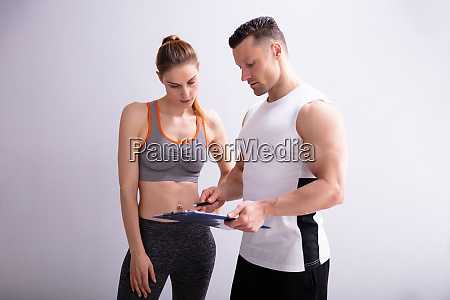 gym trainer and sporty woman discussing