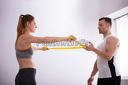 young woman with gym trainer doing