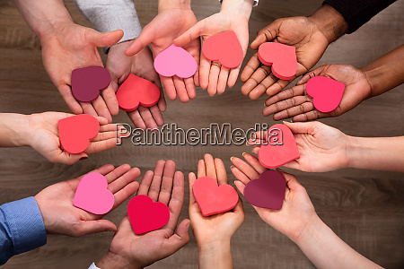 peoples hand making circle with heart