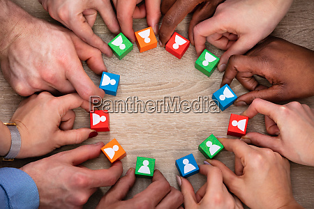 peoples hand holding colorful wooden block