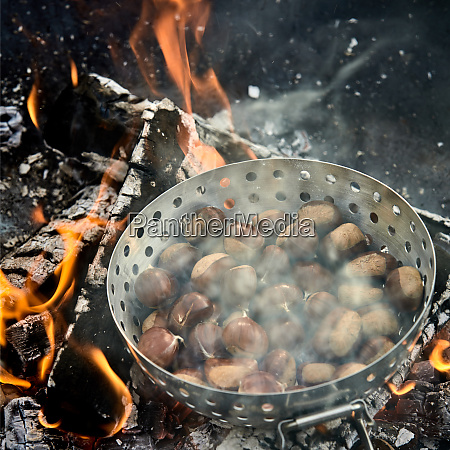 batch of fresh chestnuts sizzling over