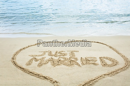just married text on sand at