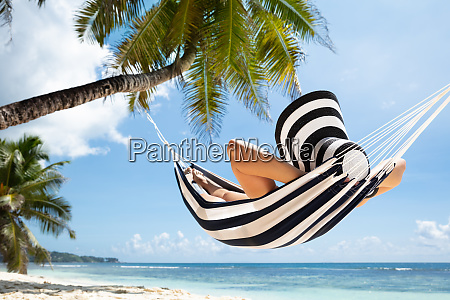 woman relaxing on hammock at beach