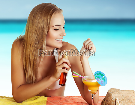 happy woman tanning on the beach