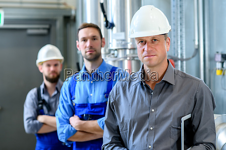 boss with two worker in factory