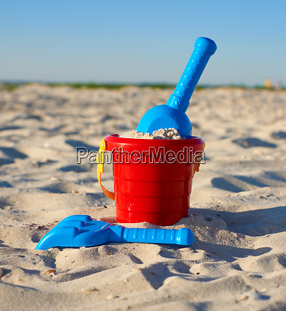 red plastic bucket and blue rake