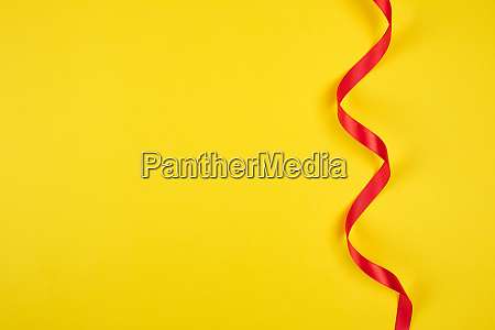 twisted red silk ribbon yellow background