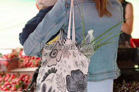 young woman buying vegetables on stall