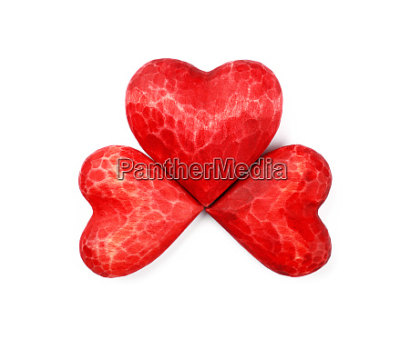 three red wooden carved hearts isolated