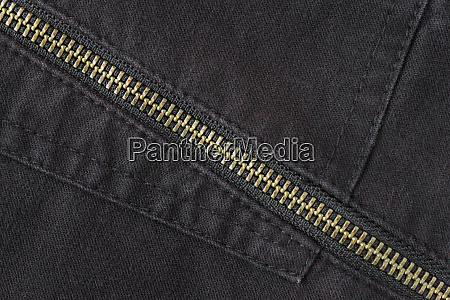 brass zip on black jeans texture