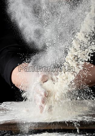 chef in black uniform sprinkles white