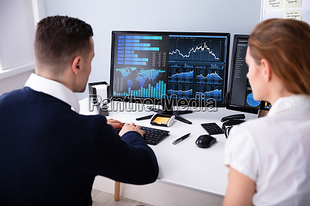 two businesspeople examining graph on computer