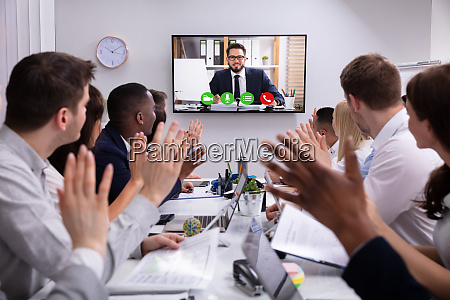 businesspeople having video conference in boardroom