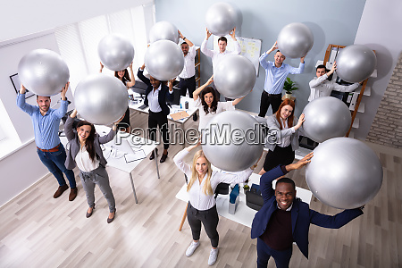 businesspeople stretching using fitness ball in