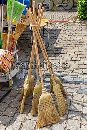 brooms for sale at a market