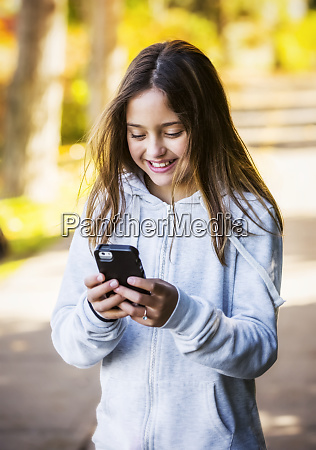 a young girl texting on a