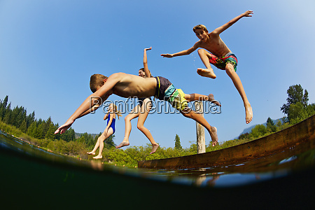 playful kids jumping off dock into