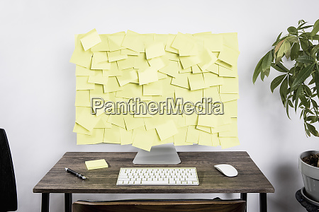 adhesive notes covering computer on desk
