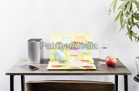 adhesive notes covering laptop on desk