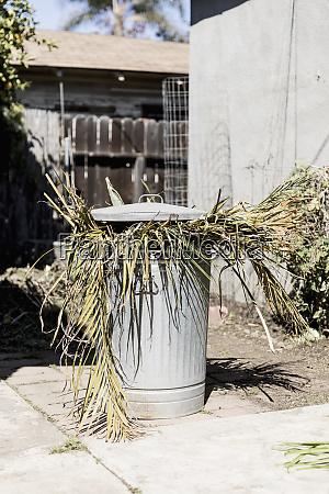 yard debris in metal garbage can