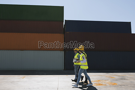 workers walking together near stack of