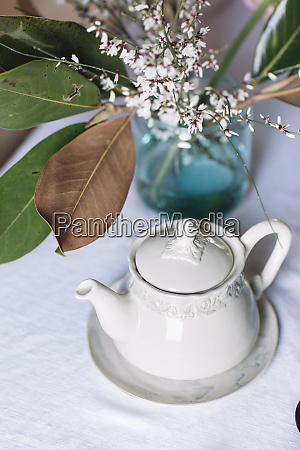 teapot and flower vase on tablecloth