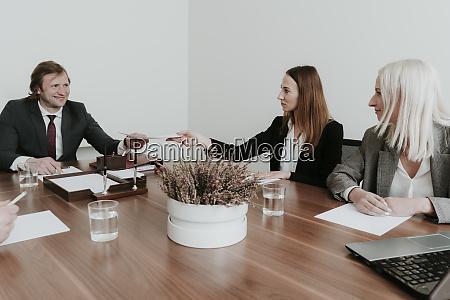 businesswoman handing over paper to colleague