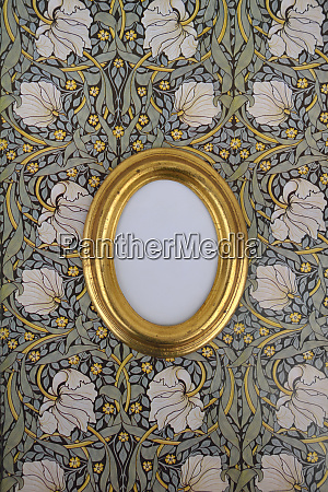 oval golden picture frame on wallpaper