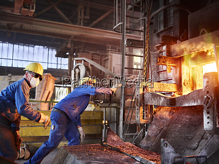 industry smeltery workers checking blast furnace