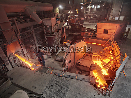 industry workers controlling smelting process