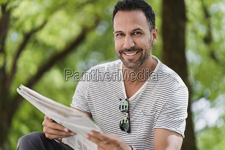 portrait of smiling man reading newspaper