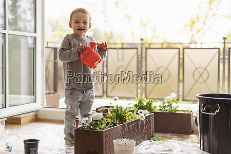 cutle little girl watering flowers at