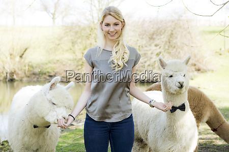 portrait of happy woman feeding alpacas
