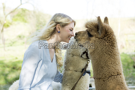happy woman cuddling her alpacas