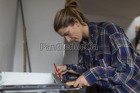 young woman assembling kitchen