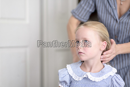 mother hairdressing her little daughter