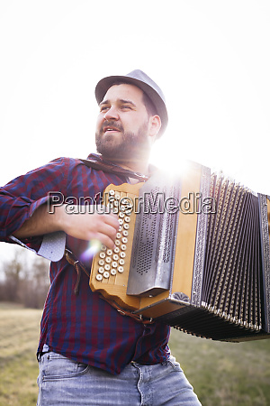 portrait of bearded man playing accordion
