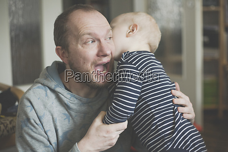 father with open mouth holding his